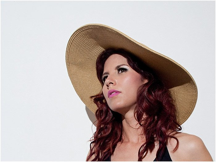 A female model posing in a straw hat for a beauty photo shoot
