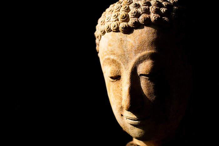 Atmospheric photo of a stone buddha taken outdoors in natural light