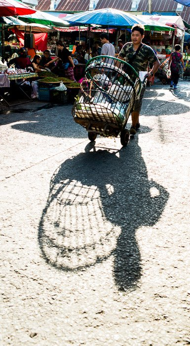 A man pushing a trolley through a market place during the best time to take photos outside in natural light