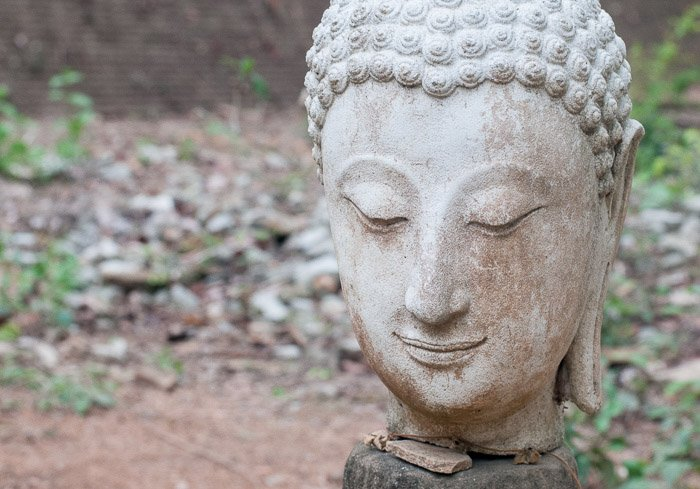 A stone statue of Buddha taken outdoors in natural light