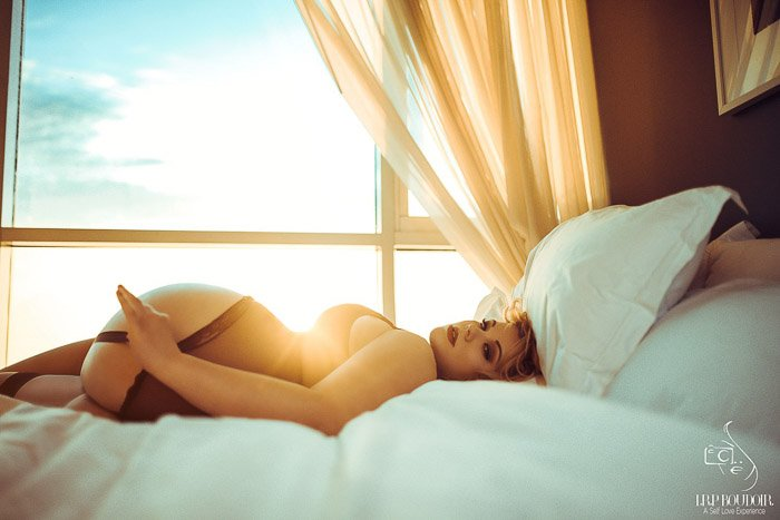 Bright and airy boudoir photo shoot of a female model posing on a bed