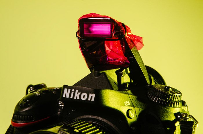 Close up of a Nikon camera with pink cellophane covering the flash - color gel photography
