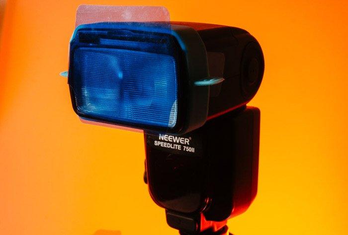 Close up of a speedlight on bright orange background