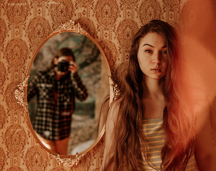 An artistic indoor portrait of a female model posing beside a mirror in which the photographer is reflected, examples of great profile pictures