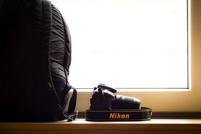 A Nikon camera placed on a shelf beside a camera backpack