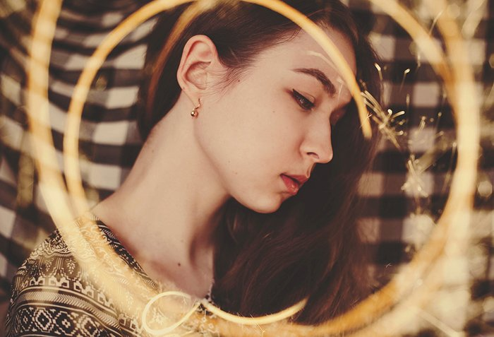 Artistic portrait of a female model posing against a diy backdrop