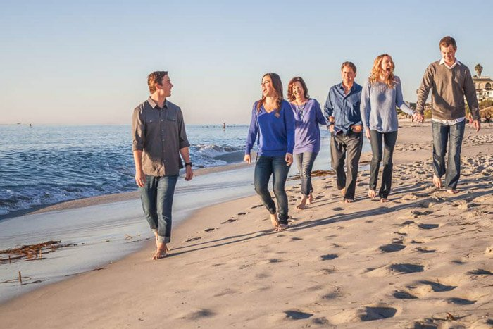 A cute family beach pictures shoot with the family walking near the shore in coordinating outfits