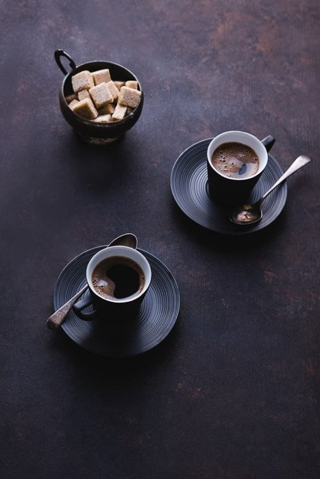 A dark and atmospheric fine art food photography still life featuring two coffee cups and sugar