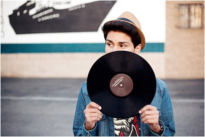A cool senior portrait of a young man posing with a vinyl record