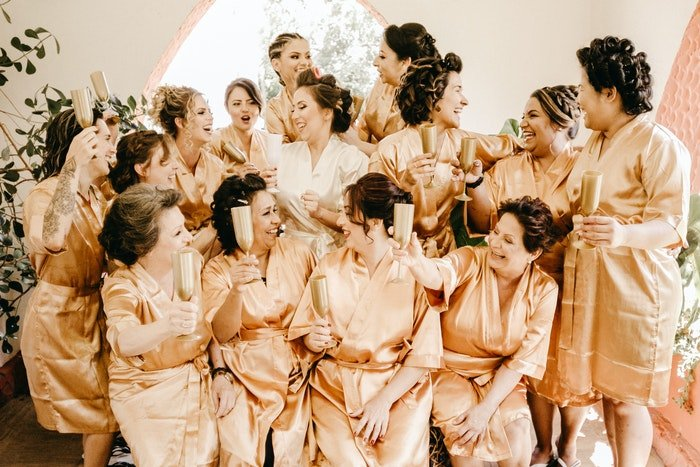 A group photo of a bridal party toasting before a wedding