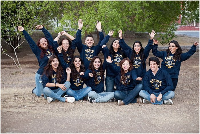A group senior photo of a group posing in class sweaters