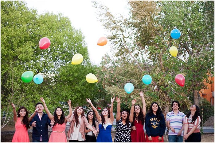 A group of seniors throwing balloons in the air