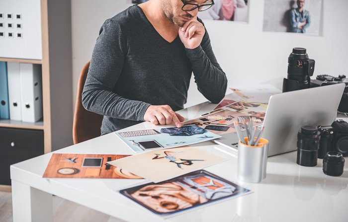 A photographer choosing prices for photography prints in a home office