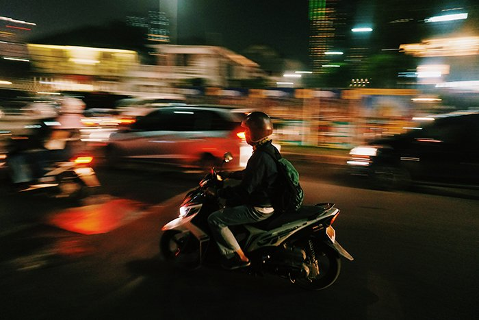 A panning shot of a motorcycle driver with blurred background of moving traffic at night