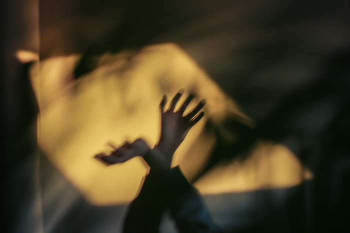 An atmospheric blurred photo of hands and shadows demonstrating impressionist photography style