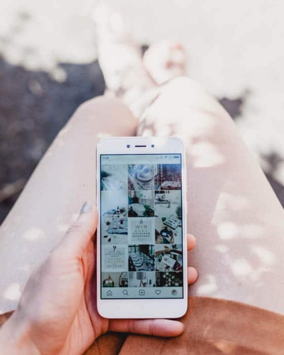 A person holding a smartphone and uploading photos to Instagram