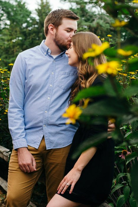 A couple embracing in a natural relaxed pose in a forest setting