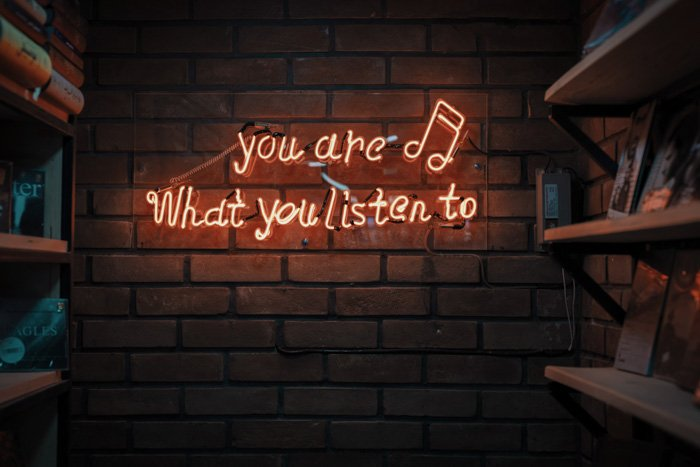 A neon sign on a brick wall, reading 'you are what you listen to'