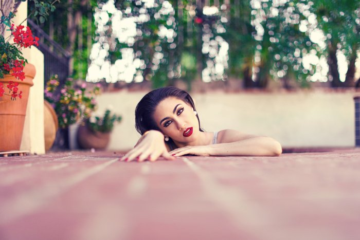 A creative portrait photo of a female model arising from pink floorboards