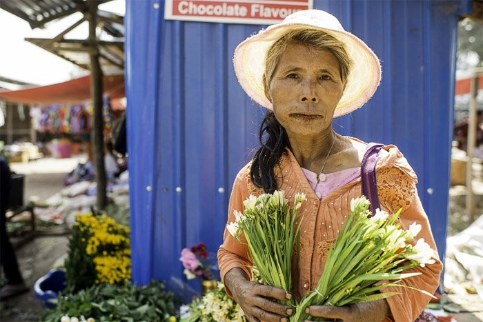 A photo of a female market vendor selling flowers, how to create white background photography