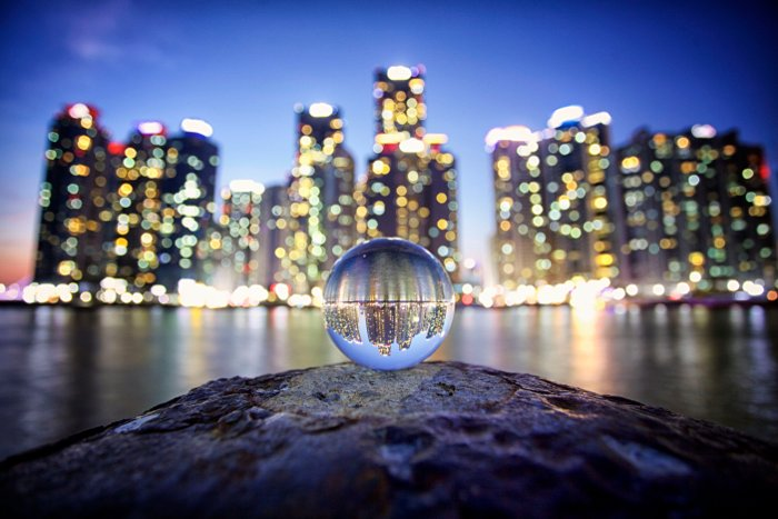 Stunning shot of a cityscape taken through a crystal ball displaying beautiful refracted light