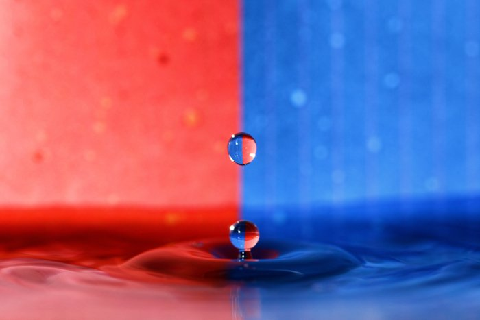 Water drop photography using refracted light against a blue and red background