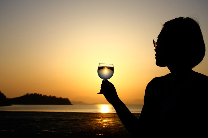 A silhouette of a female model against a beach sunset, holding a wine glass for the purpose of light refraction photography