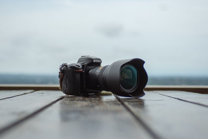A DSLR camera resting on a table outdoors - camera trade in