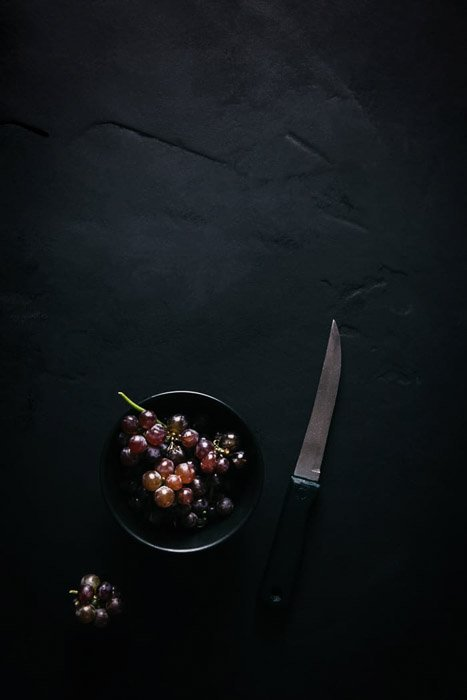 Overhead food shot of grapes in a bowl beside a knife