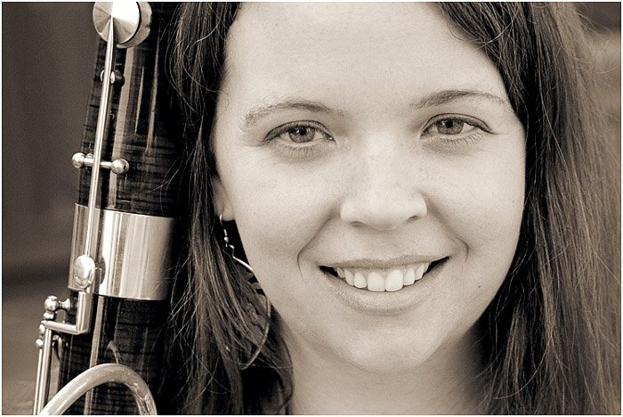 A black and white close up portrait of a female high school senior holding an instrument