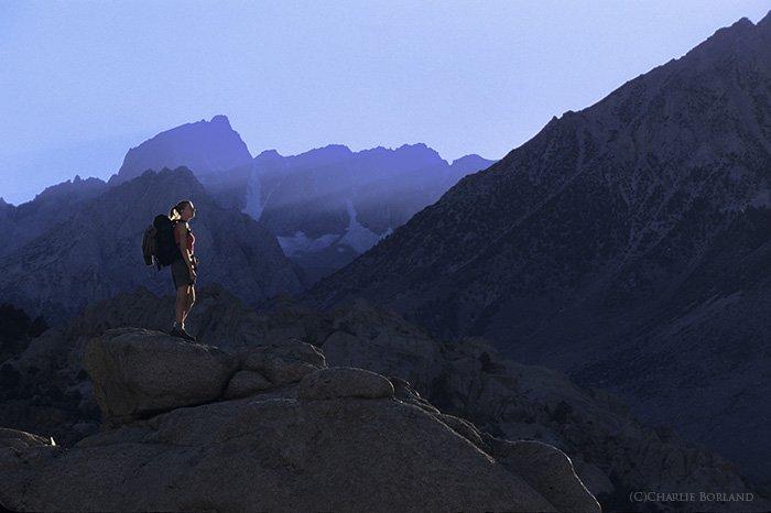 A female adventure photographer standing on rocks at the Buttermilks, Sierra Nevada, California