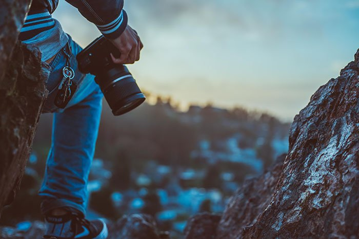 Close up of a solo adventure photographer standing on a rock and holding a dslr camera