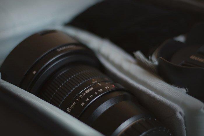 A close up of a camera lens in a camera bag - speedlight vs strobe photography