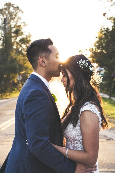 A newly wed couple kissing outdoors, shot using strobe photography