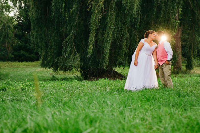 A newly wed couple kissing outdoors, shot with speedlight flash lighting