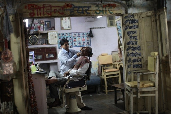 A candid shot of a barber shaving a client - street photography camera settings