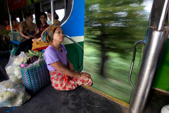 A woman sitting at the edge of a moving train, creative motion blur in the background. Street photography camera settings.