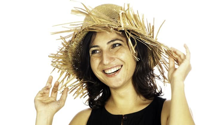 portrait of a female model in a straw hat posing against a white photography background