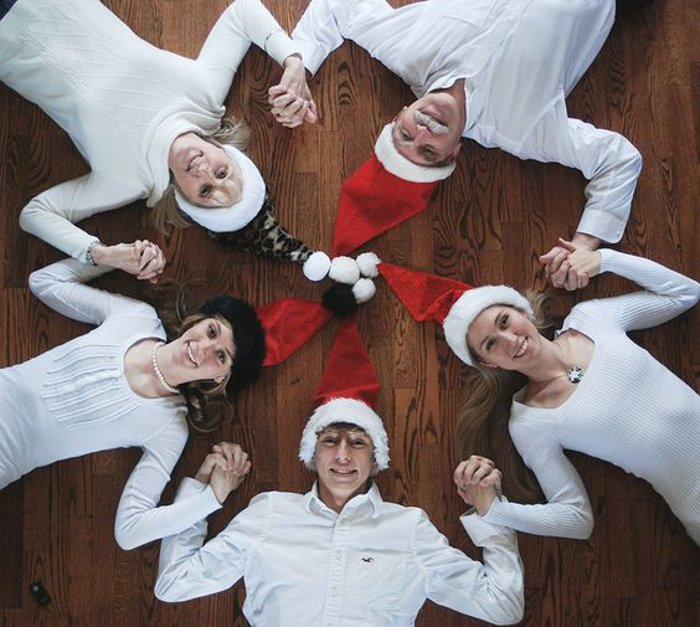 A family photo shoot of five people in Christmas hats lying on the floor