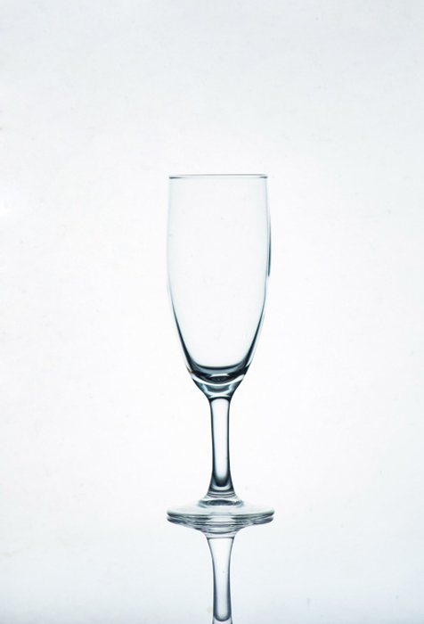 A photo of a champagne glass on white background - glass photography tips
