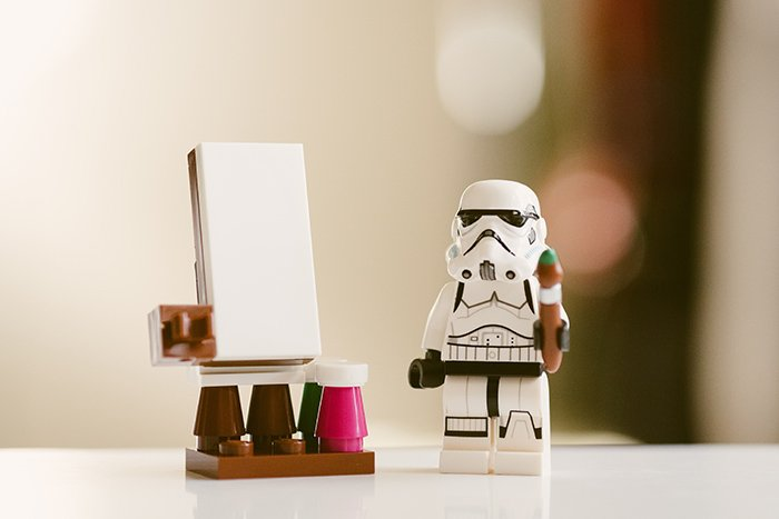 Cool close up toy photography of a lego storm trooper painting on a toy easel