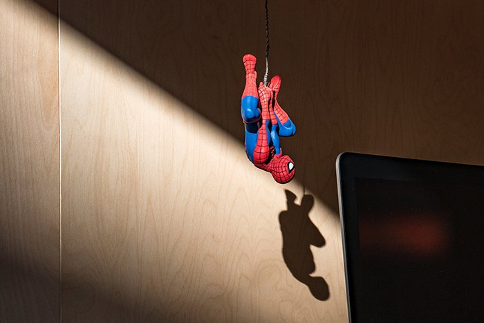 Spiderman action figure photography hanging from a rope