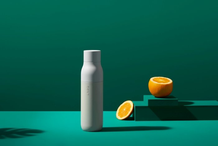 White water bottle with an orange on a green background