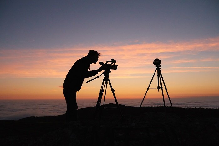 Silhouette of a photographer shooting with a DSLR on a tripod at sunset