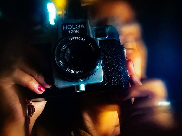 A person shooting with a holga camera, photo processed with a creative blur app