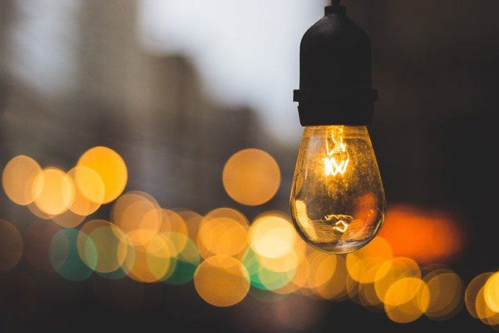 A lightbulb in the foreground of blurry bokeh lights