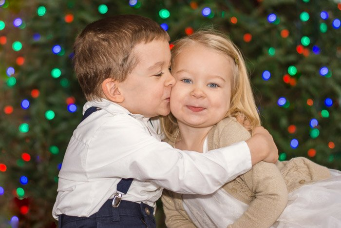 Two young children embracing with blurred background of Christmas lights