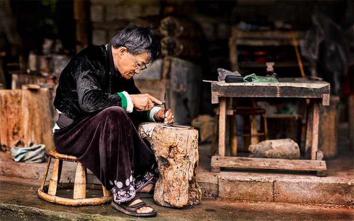 A portrait of a Hmong blacksmith at work created using the brenizer method