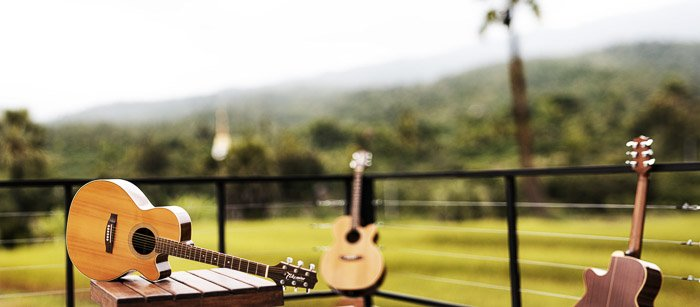 A guitar resting on an outdoor table shot with wide angle lens
