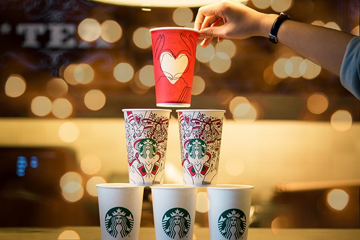 A stack of Christmas themed cups with bokeh lights in the background